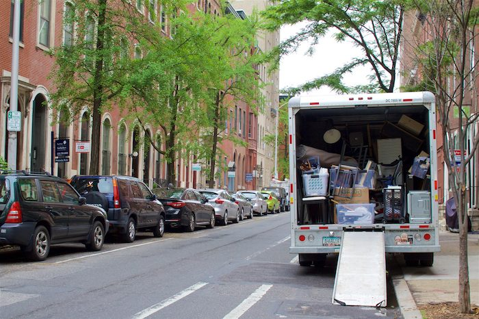 A moving truck packed with items to move on a busy street.