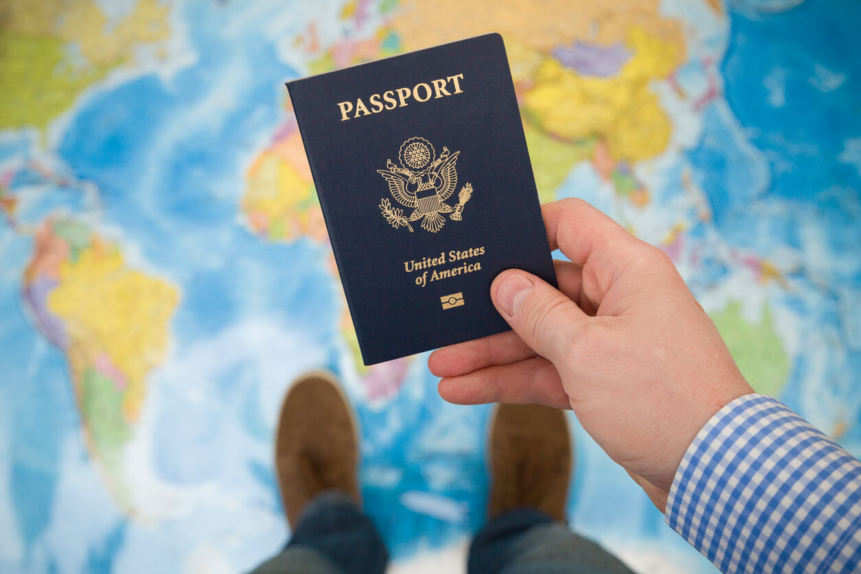 A person holding a passport in their hand. In the background, a map of the world is visible.