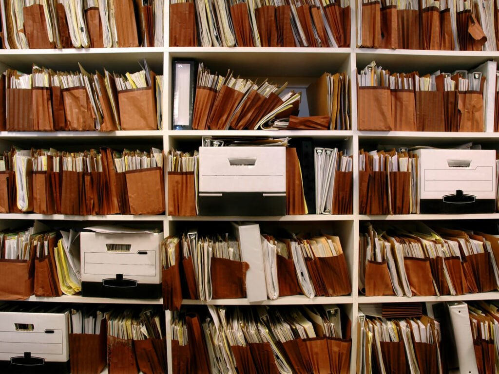 Office shelves overstuffed with file folders and banking boxes.