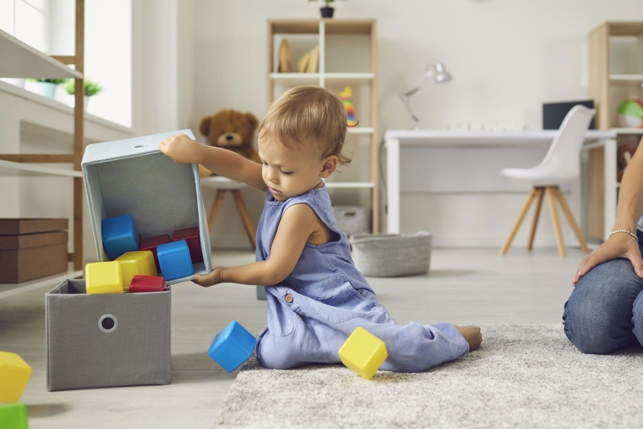 child dumping blocks from one fabric bin into another