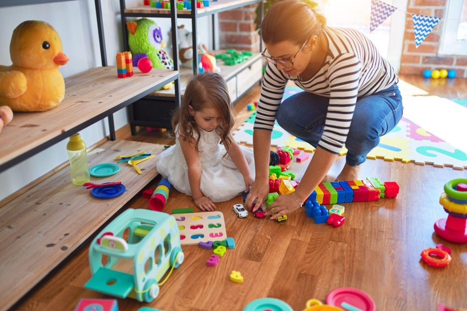 mother and child cleaning up toys in a  playroom